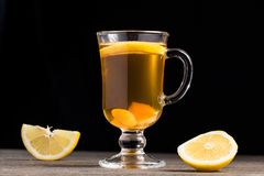 A cup of ginger tea with lemon on a wooden background. A transparent glass filled with ginger tea with lemon. On a blue wooden table. Yellow lemon Stock Images