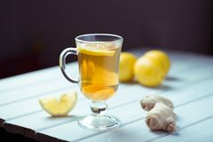 A cup of ginger tea with lemon on a wooden background. A transparent glass filled with ginger tea with lemon. On a blue wooden table. Yellow lemon Stock Photos