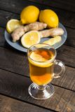 A cup of ginger tea with lemon on a wooden background. A transparent glass filled with ginger tea with lemon. On a blue wooden table. Yellow lemon Stock Photography