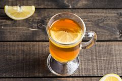 A cup of ginger tea with lemon on a wooden background. A transparent glass filled with ginger tea with lemon. On a blue wooden table. Yellow lemon Royalty Free Stock Images