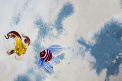 Transparent glass fishes on a blue white background Royalty Free Stock Photos