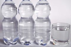 A transparent glass full of water. near a bottle of mineral water. Stock Photo