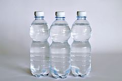 A transparent glass full of water. near a bottle of mineral water. Royalty Free Stock Photo