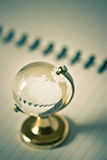 Transparent glass globe. On white spiral note book Stock Photo