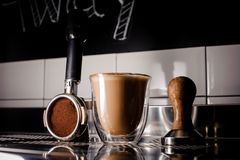 Transparent glass of a hot coffee and barista essentials. Beautiful transparent glass of a delicious hot coffee and different barista essentials standing on the Stock Images