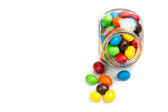 Transparent glass jar with colorful chocolate candies on white b Royalty Free Stock Image
