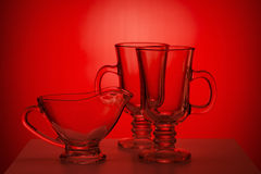 Transparent glass jug and glassfuls on red Stock Images