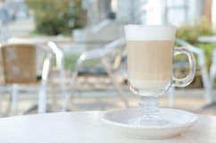 Transparent glass with latte or cappuccino. In the background a blurry cafe. All in bright colors royalty free stock photography