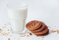 Transparent glass of milk and cookies on a white background Stock Photos