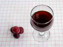 Transparent glass with red wine and few sweet red grapes on white pink checkered tablecloth. Front view.  royalty free stock image