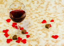 Transparent glass with red wine, heart chocolate and textile red valentine hearts, old paper background, close up Stock Photos