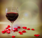 Transparent glass with red wine and textile red valentine hearts, light lens flare background, close up Stock Photo