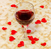 Transparent glass with red wine and textile red valentine hearts, old paper background, close up Royalty Free Stock Photos