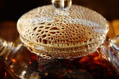Transparent glass teapot with black tea on a brown background. Bubbles on a cover of a transparent glass teapot of black tea on a brown background Royalty Free Stock Photo