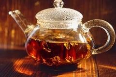 Transparent glass teapot with black tea on a brown background. The transparent glass teapot of black tea with the bubbles on a cover on a brown background Stock Photo