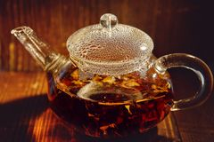 Transparent glass teapot with black tea on a brown background. The transparent glass teapot of black tea with the bubbles on a cover on a brown background Royalty Free Stock Photography