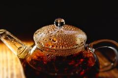 Transparent glass teapot with black tea on a brown background. The transparent glass teapot of black tea with the bubbles on a cover on a brown background Royalty Free Stock Photos