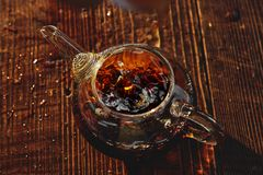 Transparent glass teapot with black tea on a brown background. The transparent glass teapot of black tea with the splash on a brown background Royalty Free Stock Photography