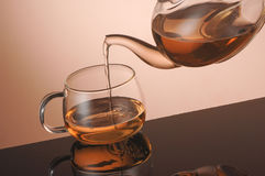Transparent glass teapot and cup with tea Stock Images