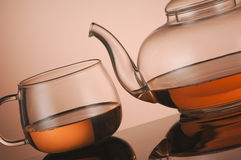 Transparent glass teapot and cup with tea Stock Photo