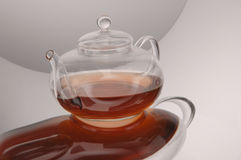 Transparent glass teapot and cup with tea Stock Photos