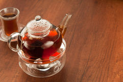 Transparent glass teapot and cup with tea Royalty Free Stock Photos