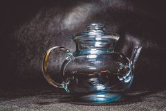 Transparent glass teapot for tea on a black monophonic background. Beautiful ware. stock image