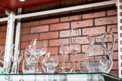 Transparent glass utensil on metal shelf Royalty Free Stock Photography