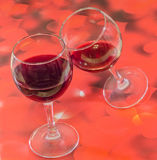 Transparent glasses with red wine, red hearts background, close up Stock Images