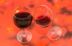 Transparent glasses with red wine, red hearts background, close up Stock Photos