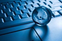 Transparent globe on a laptop  keyboard Stock Photos