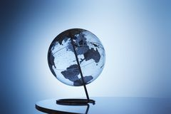 Transparent globe on stand in studio Stock Photography