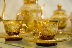 Transparent gold hand-made tea-service. Transparent gold hand-made cup and saucer covered with gold drawing Stock Image