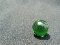 Transparent and green glass Marble. A green marble made of glass. Transparent and alone royalty free stock photos