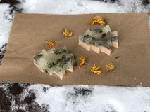 Transparent handmade soap in the form of Christmas trees with herbs on a background of rough paper stock images