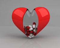 Transparent heart with pills inside over grey Stock Images