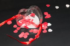 Transparent heart with ribbon and hearts in it. Transparent heart with red ribbon and some red and white hearts in it on a black background Stock Photos