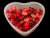 Transparent heart shape vase (bowl) filled with colored (red) heart shape jellies, black background, close up. Transparent heart shape vase (bowl) filled with stock photo
