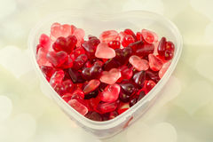 Transparent heart shape vase (bowl) filled with colored (red) heart shape jellies, light hearts background, close up. Stock Photography