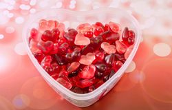 Transparent heart shape vase (bowl) filled with colored (red) heart shape jellies, red bokeh background, close up. Transparent heart shape vase (bowl) filled stock photography