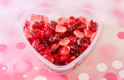 Transparent heart shape vase (bowl) filled with colored (red) heart shape jellies, red bokeh background, close up. Transparent heart shape vase (bowl) filled royalty free stock photos