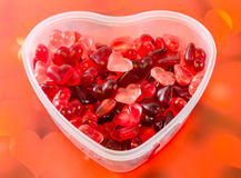 Transparent heart shape vase (bowl) filled with colored (red) heart shape jellies, red hearts background, close up. Transparent heart shape vase (bowl) filled royalty free stock image