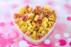 Transparent heart shape vase (bowl) filled with colored (red, yellow an orange) heart shape pasta, colored degradee background. Transparent heart shape vase ( stock images
