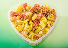 Transparent heart shape vase (bowl) filled with colored (red, yellow an orange) heart shape pasta, colored degradee background. Transparent heart shape vase ( stock photo