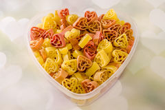 Transparent heart shape vase (bowl) filled with colored (red, yellow an orange) heart shape pasta, colored degradee background. Transparent heart shape vase ( stock image