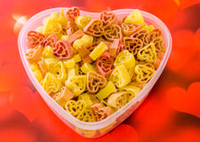 Transparent heart shape vase (bowl) filled with colored (red, yellow an orange) heart shape pasta, colored degradee background Royalty Free Stock Image