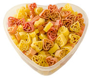 Transparent heart shape vase (bowl) filled with colored (red, yellow an orange) heart shape pasta, white background. Close up royalty free stock image