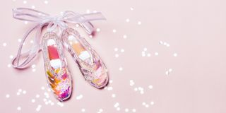 Transparent Holographic Christmas Toy Pointe Shoes and sparkle confetti on pink pastel background.  royalty free stock photos
