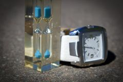 Transparent hourglass with blue sand and watch with white clock face