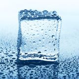 Transparent ice cube with reflection on blue glass with water drops Royalty Free Stock Images